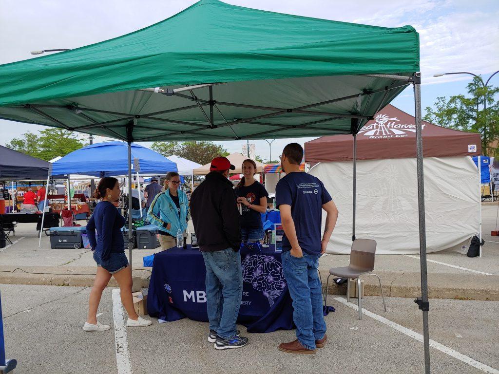 Trainees Lauren Grant, Karla Ramos-Cruz, and Jorge Maldonado De-Jesus talk to a market attendee.