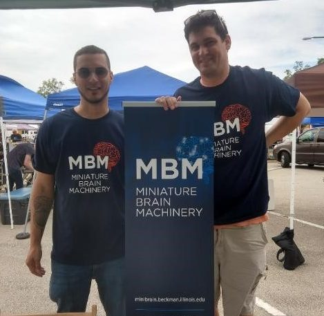 Jorge Maldonado De-Jesus and Brian Baculis standing in front of the MBM booth