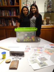 A photo of two young women behind a table. On the table is a plastic bin. In front of the plastic bin are a number of artifacts, including facsimile currency from several nations, a replica clay tablet, a container of PlayDough, and a stylus.
