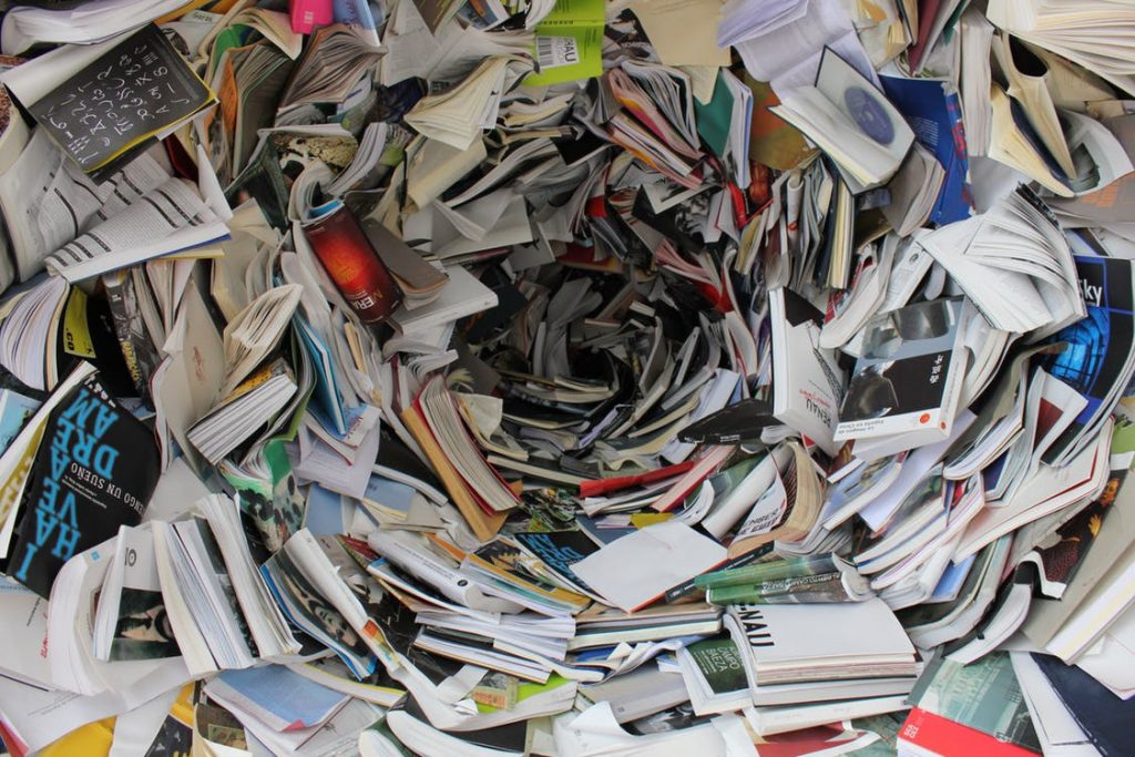 A circular and messy pile of books and papers.