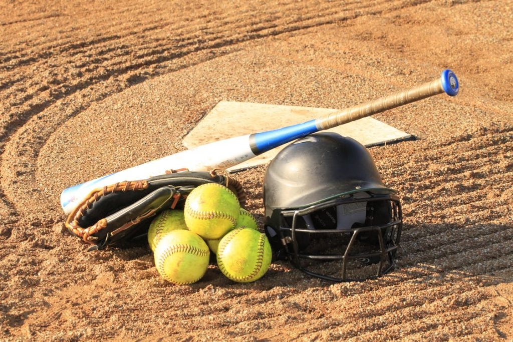 A small stack of baseballs, a helmet, and a baseball bat resting in the sand near a base.