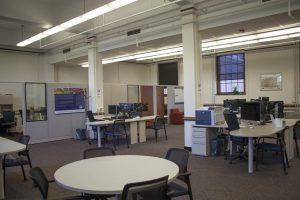 The Scholarly Commons space. it contains several workstations with a carpeted floor.