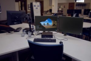 A dual-monitor computer in the Scholarly Commons. The background of the image shows the Scholarly Commons space, which is filled with out dual-monitor computers and various desks.