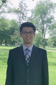 Headshot of Wenjie Wang, wearing a black suit with a blue shirt and blue striped tie. Standing in front of trees.