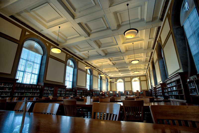 Reading room of the Main Library at the University of Illinois. Large room with tall white ceiling, large windows, light fixtures, and wooden tables and chairs.