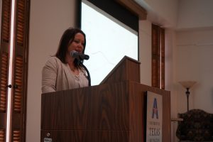 Michelle Reed giving a presentation at a podium