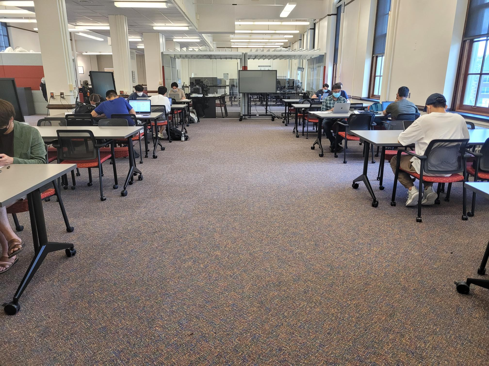 Study tables arranged in two rows with students studying.