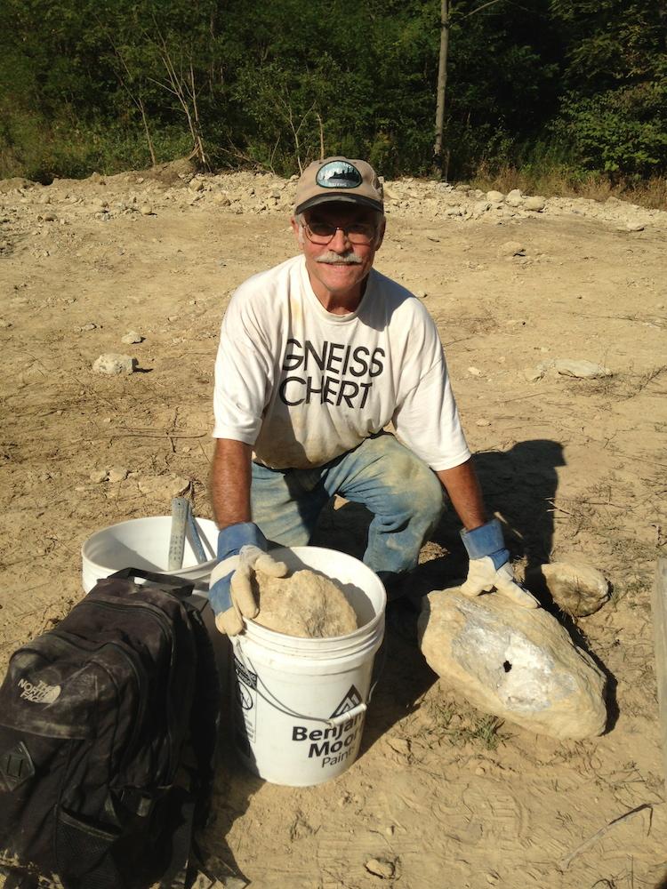 Man with cap kneeling in mud