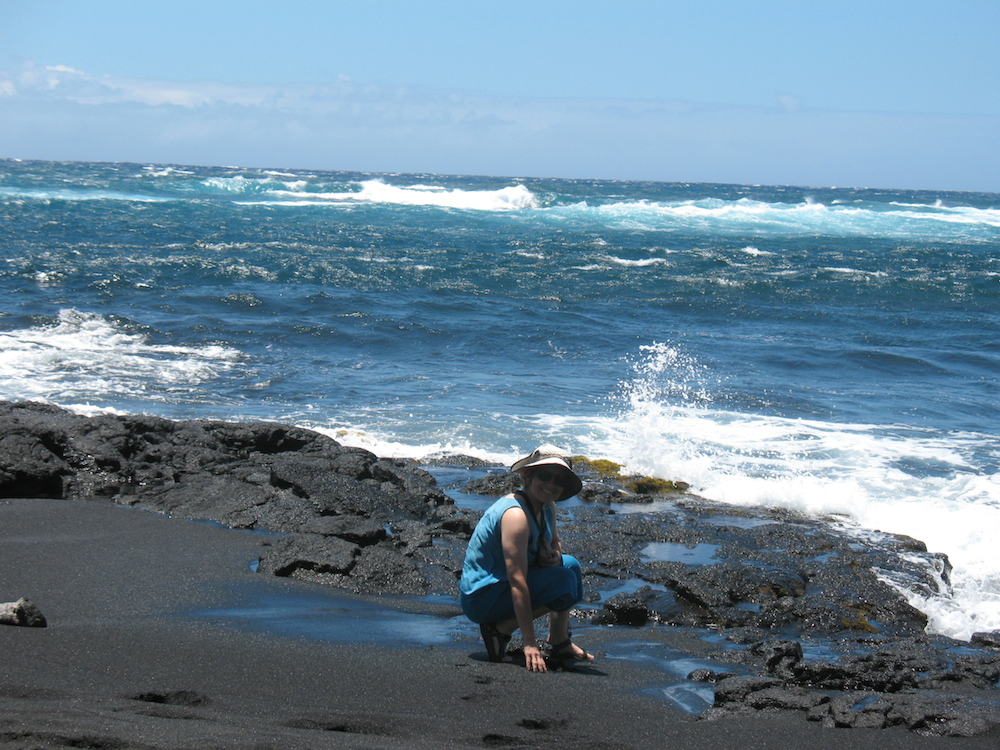 Black sand with blue seawater & sky