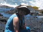 Woman with hat, black rocks in background