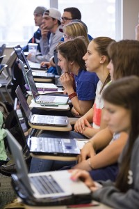 Students listen to a lecture while taking notes on laptop computers.