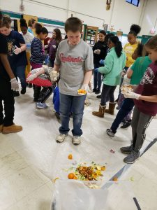 Elementary students sorting food waste in a school cafeteria
