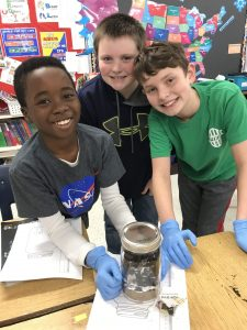 Three boys gather around the jar they are working on and smile at the camera