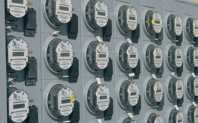 a large wall full of round electrical meters