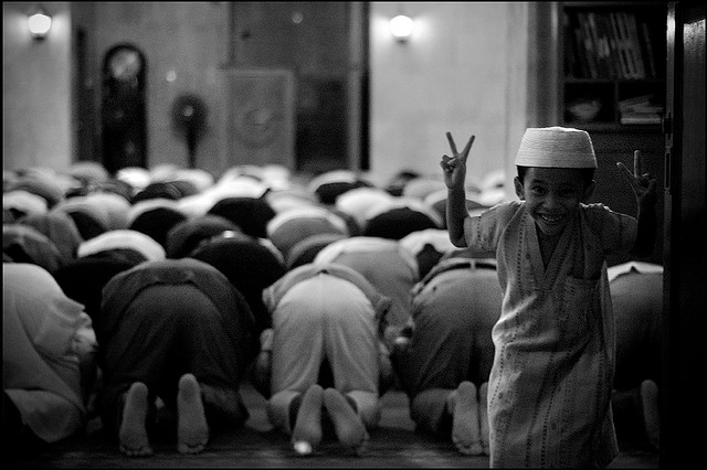 A group of Muslim men bowed in prayer and a young boy playing. Photo Credit: Daniel Bayona