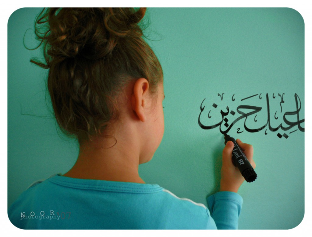 A girl writes Arabic calligraphy on a wall. Image Credit: Nur Meryem Seja on Flickr