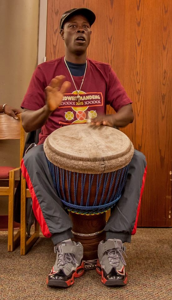 Bolokada plays djembe at a demonstration at the Urbana Free Library at Midwest Mandeng 2015.