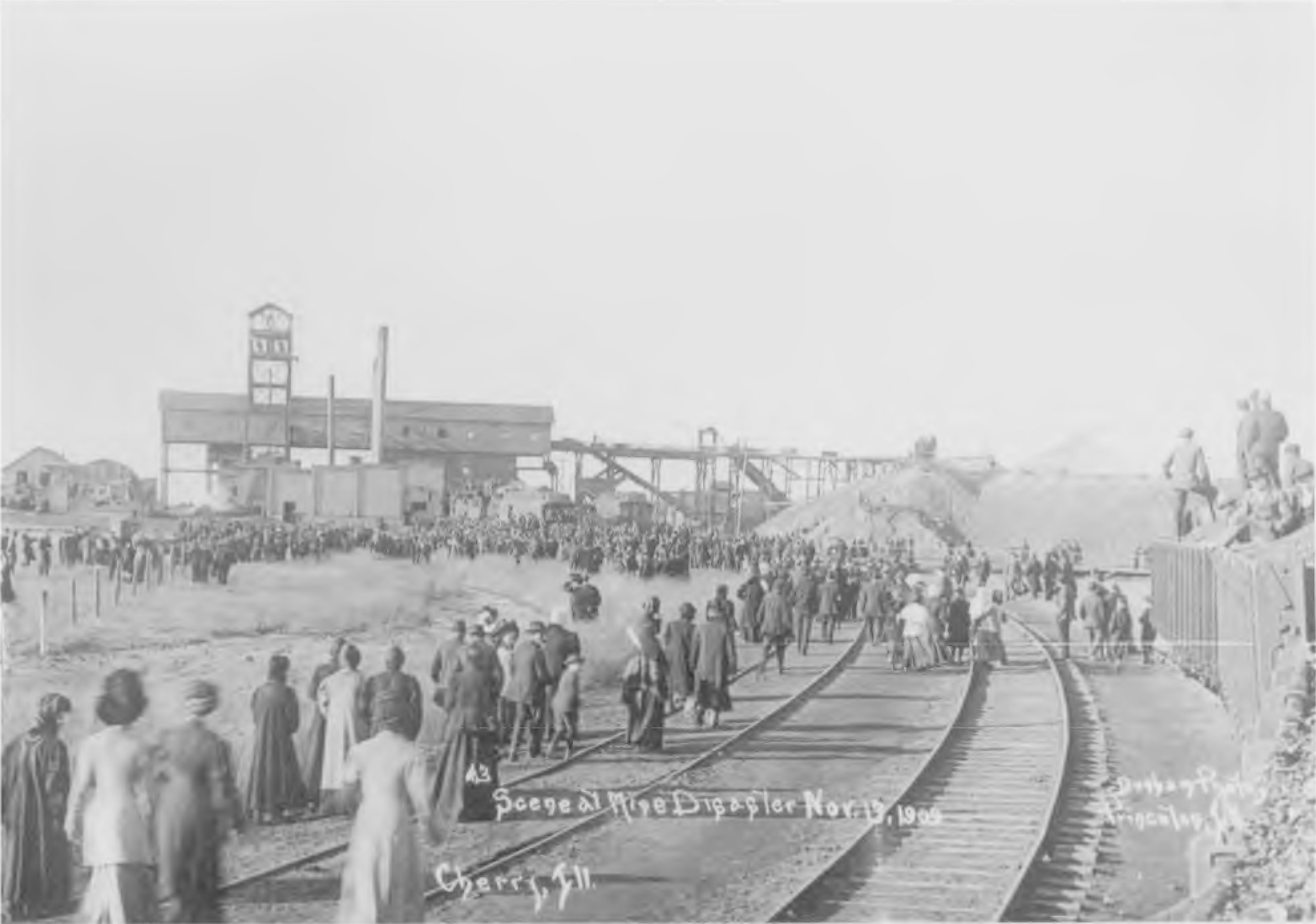 Photograph of scene at Cherry Mine Disaster, in which a crowd walks along railroad tracks toward the mine, 1909.