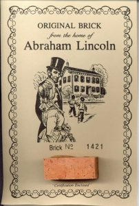Souvenir brick on card with Illustration of the Lincoln family and their Springfield home