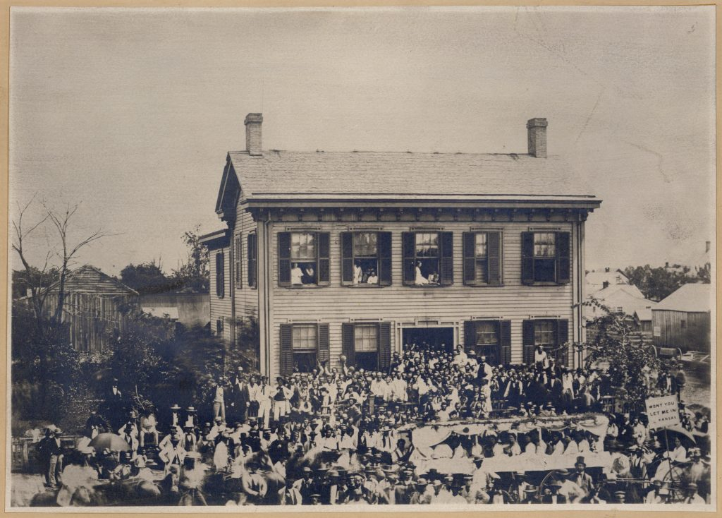 Black and white photo of Lincoln's home in Springfield during a procession, with Lincoln standing to the right of the door.