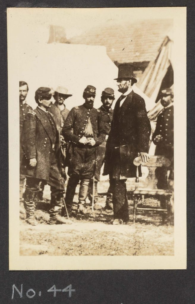 Black and white photo showing Lincoln standing with Union soldiers