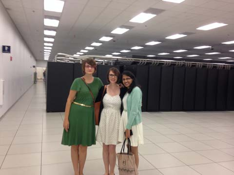 Three women pose in front of a bank of computers.