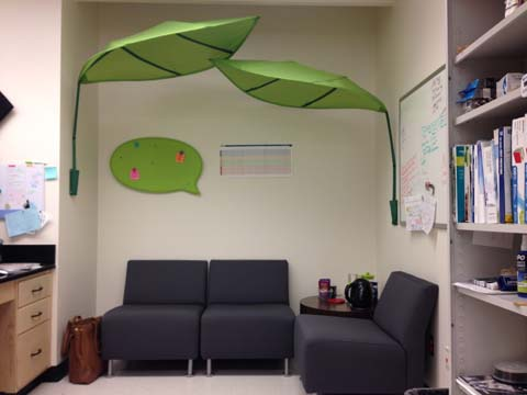 The corner of a room with grey chairs, a canopy of oversized leaves, and a speech bubble-shaped green bulletin board.