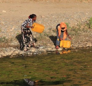 Two Ethiopian woman filling buckets from a stream.