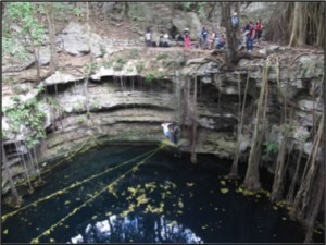 People gathered at the edge of a cenotes.