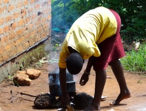 An African man boiling water.