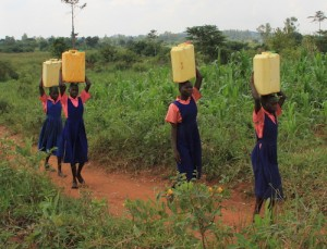 Four African school children in uniforms carrying water