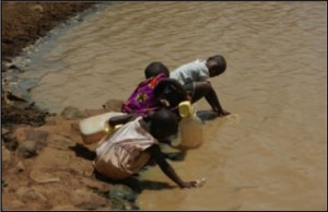 Three african children collecting water from a muddy pool.
