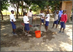 Uniformed African school children filling a bucket at a well.