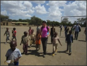 A Caucasian woman speaking with African school children in a playground.