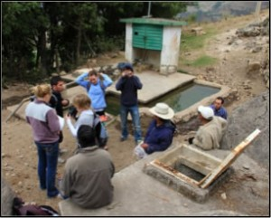 Casually dressed researchers and Mexicans near a well