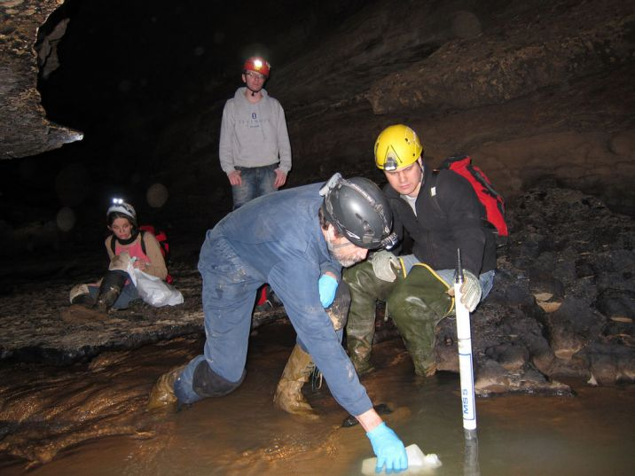 man collects water sample in cave