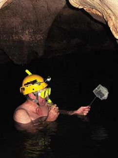 man up to his shoulders in water in a cave