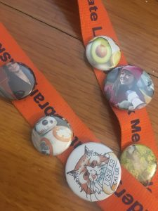 An orange UGL lanyard with homemade buttons of an avocado, tatiana maslany, a dog in a field, Uggles, BB-8, and tina fey