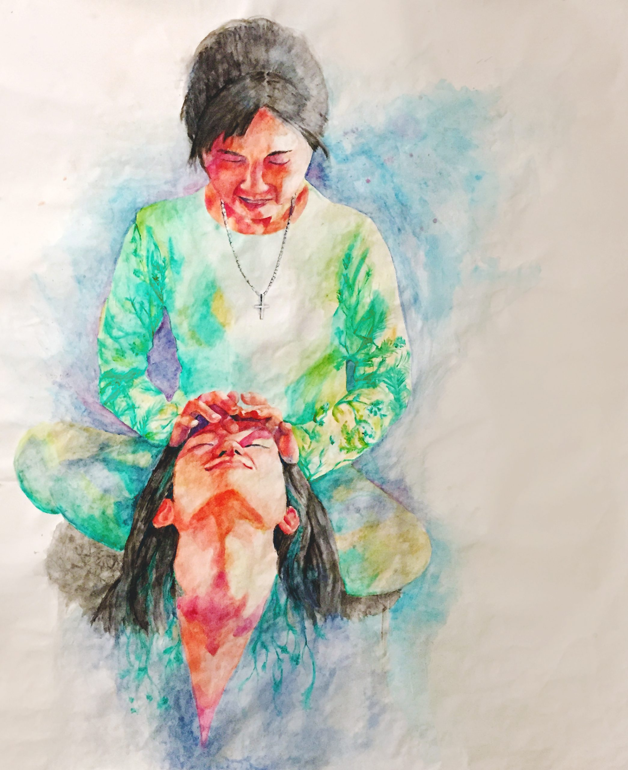 A person wearing blue with their head tilted back receives a massage from their mother, seated above them, wearing green and a cross necklace.