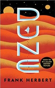 Book cover with orange and yellow waves and figure of a man walking into the distance. Title Dune