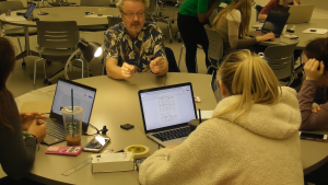 Students with laptops and lab equipment sit at a table talking to their professor.