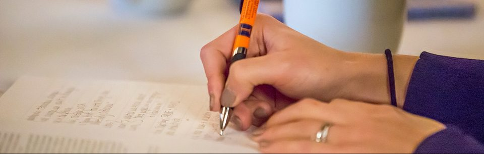 A close-up image of a woman's hand. She is holding a pen and taking notes. There is a mug of coffee sitting beside her.