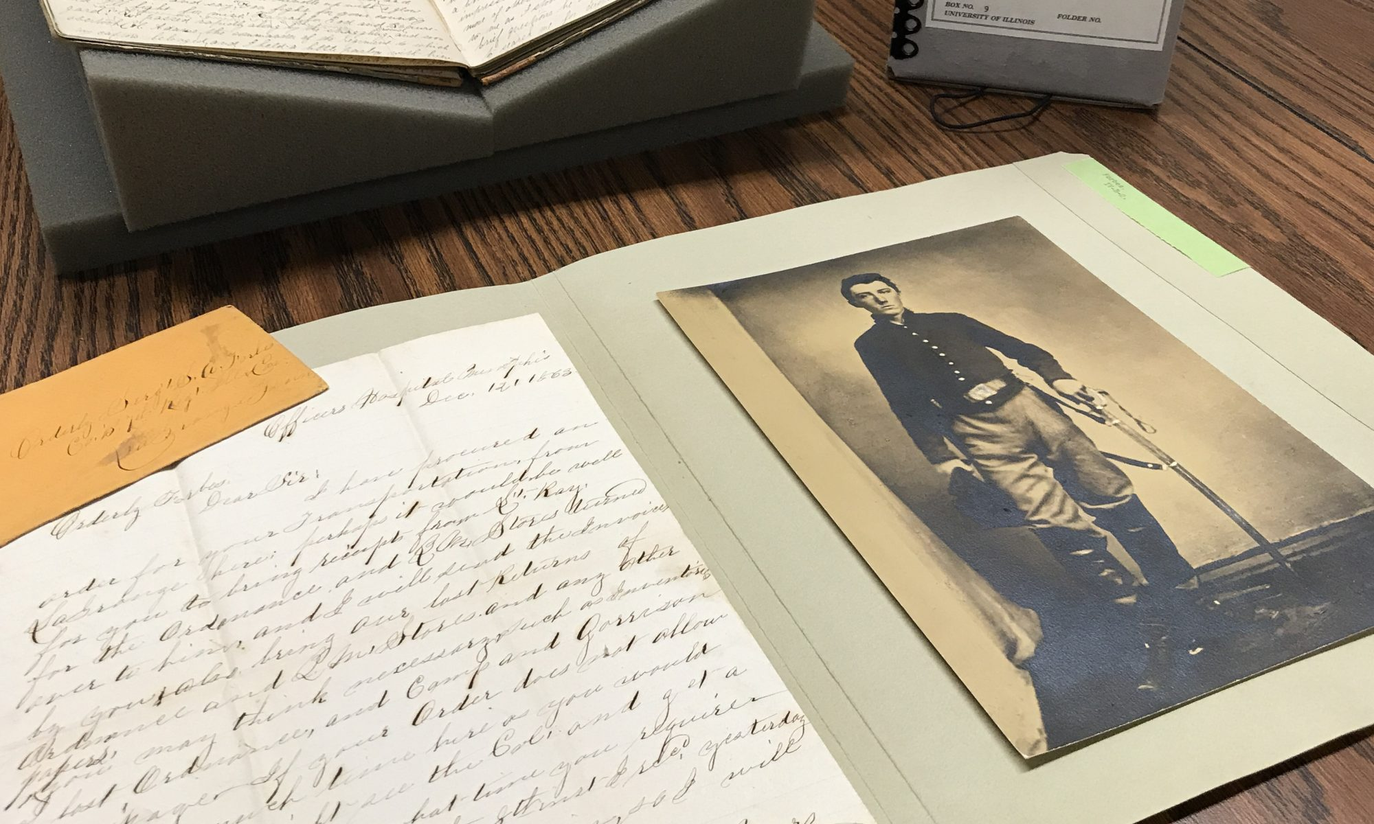 Picture of an open archival folder containing a Civil War letter and envelope as well as a photograph of a Civil War soldier. Image also includes an open diary on book supports and an archival box. All items are found in the Stephen A. Forbes Collection at the IHLC.