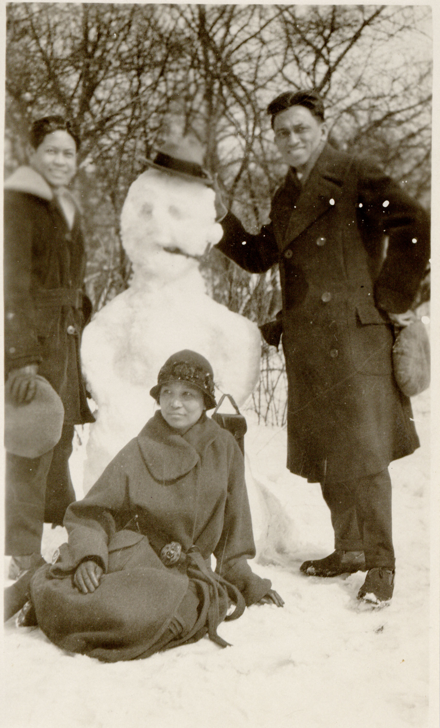 Photograph of Alayu family gathered around a snowman.