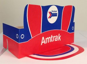A red and blue paper conductor's hat with the Amtrak logo printed on the front center.