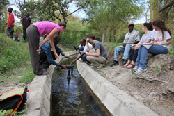 Individuals on either side of an irrigation canal
