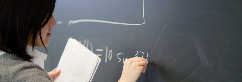 A woman holding a spiral-bound notebook writes an equation on a blackboard.
