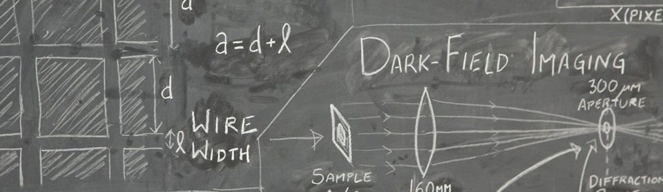 "A close-up picture of a blackboard with physics diagrams. The equation a=d+l can be read, along with the words ""dark-field imaging"" and an accompanying diagram of a diffraction array."