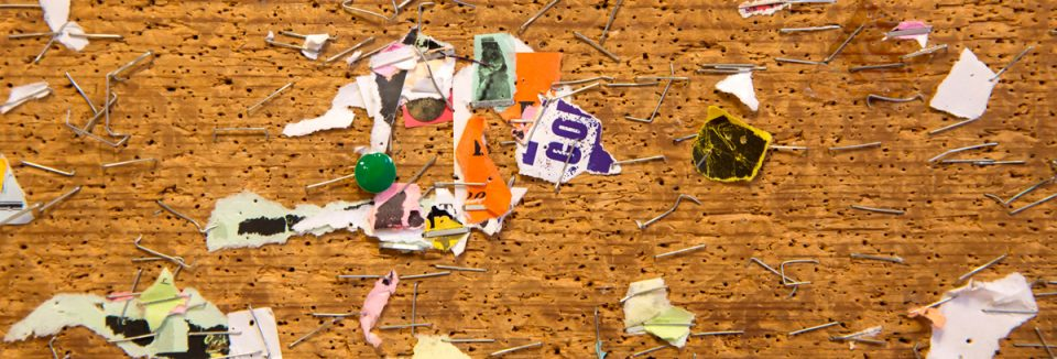 Abstract of staples, and paper remnants on a bulletin board in the University of Illinois Davenport Hall